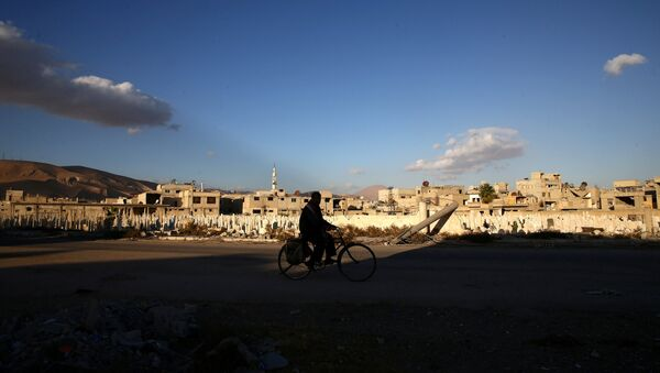 A man rides a bicycle near a cemetery in the rebel held besieged town of Douma, eastern Ghouta in Damascus, Syria - Sputnik International