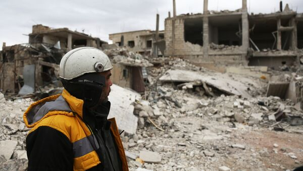 Forty-five-year-old Samir Salim (L) who along with his three brothers are members of the White Helmets rescue forces looks out at destroyed buildings in the town of Medeira in Syria's rebel-held Eastern Ghouta area on February 12 2018. - Sputnik International