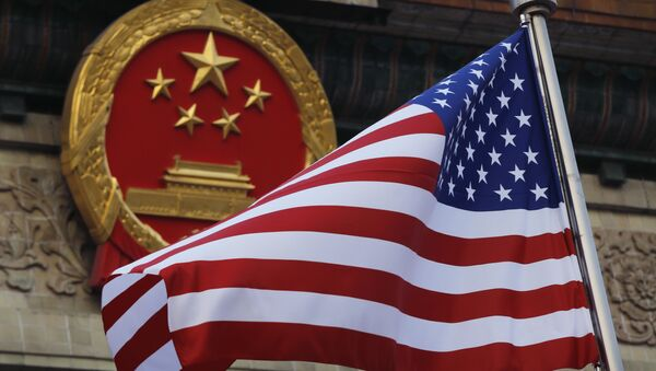 FILE - In this Nov. 9, 2017 file photo, an American flag is flown next to the Chinese national emblem during a welcome ceremony for visiting U.S. President Donald Trump outside the Great Hall of the People in Beijing - Sputnik International