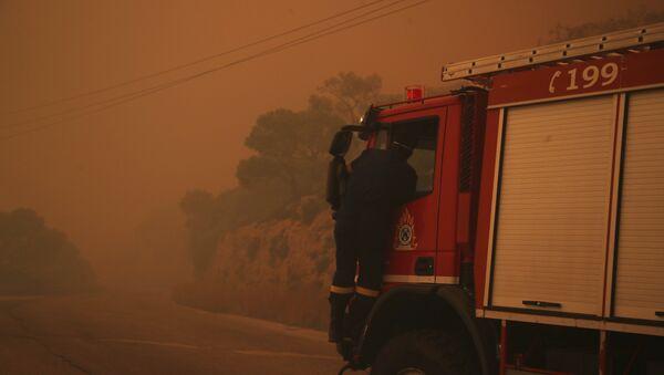 A fire truck is engulfed in a pall of orange smoke on a road near Kineta, west of Athens, Monday, July 23, 2018. - Sputnik International