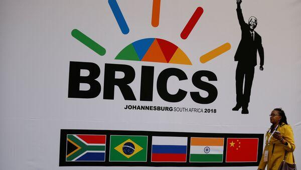 A delegate walks past a BRICS logo ahead of the 10th BRICS Summit, in Sandton, South Africa, July 24, 2018 - Sputnik International