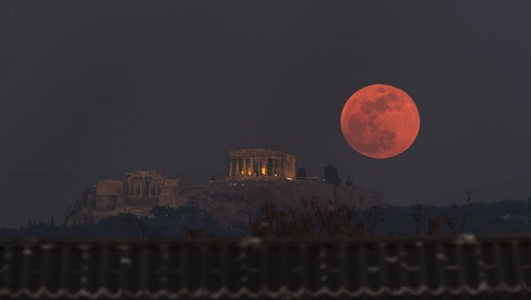 A boat sails in the Bosporus Strait separating Europe and Asia, as a super blue blood moon rises over Istanbul, Wednesday, Jan. 31, 2018. It's the first time in 35 years a blue moon has synced up with a supermoon and a total lunar eclipse, or blood moon because of its red hue, all rolled into one celestial phenomenon - Sputnik International