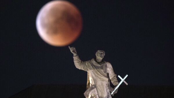 The moon turns red during a total lunar eclipse, as seen from Dresden, Germany, Friday, July 27, 2018. Skywatchers around much of the world are looking forward to a complete lunar eclipse that will be the longest this century.  - Sputnik International
