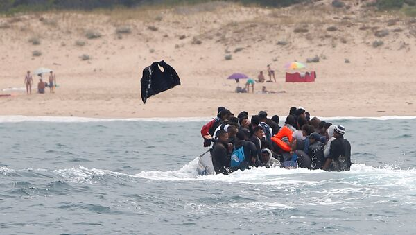 Migrants throws up a life-vest before disembarking from a dinghy at Del Canuelo beach after they crossed the Strait of Gibraltar sailing from the coast of Morocco, in Tarifa, southern Spain, July 27, 2018 - Sputnik International