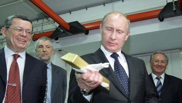 January 24, 2011. Russian Prime Minister Vladimir Putin holding a gold bar while visiting the Central Depository of the Bank of Russia. Georgy Luntovsky (left), first deputy chief of the Central Bank of Russia - Sputnik International