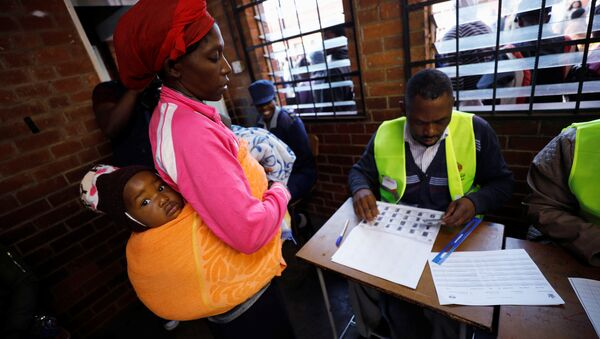 A Zimbabwean voter registers to cast her ballot in the country's general elections in Harare, Zimbabwe, July 30, 2018 - Sputnik International