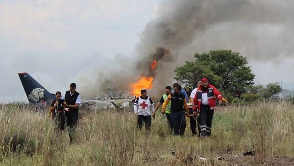 In this photo released by Red Cross Durango communications office, Red Cross workers and rescue workers carry an injured person on a stretcher, right, as airline workers, left, walk away from the site where an Aeromexico airliner crashed in a field near the airport in Durango, Mexico, Tuesday, July 31, 2018 - Sputnik International