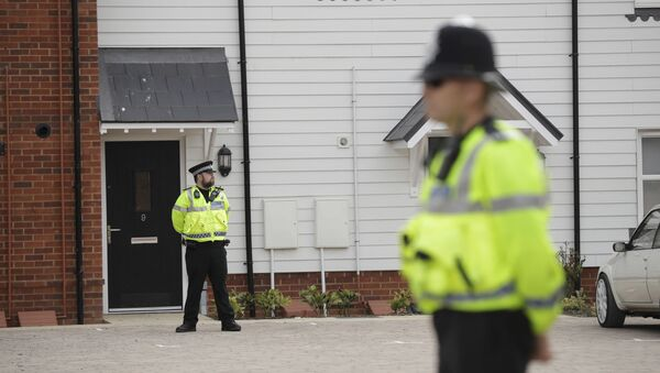 British police officers stand outside the front door of a residential property in Amesbury, England, Wednesday, July 4, 2018. British police have declared a major incident after two people were exposed to an unknown substance in the town, and are cordoning off places the people are known to have visited before falling ill - Sputnik International