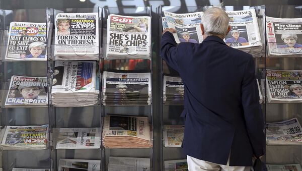 A man picks up a newspaper reporting the development following Britain's general election at a shop in Westminster in London, Saturday June 10, 2017 - Sputnik International