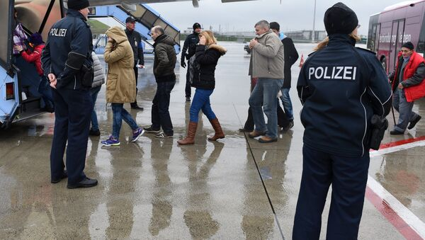 Police officers escort rejected refugees who are boarding an aircraft at the airfield of the Franz-Josef-Strauss airport in Munich, southern Germany, on December 9, 2015, as the plane brings rejected asylum seekers back to their country - Sputnik International