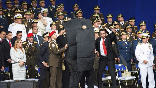 In this photo released by China's Xinhua News Agency, security personnel surround Venezuela's President Nicolas Maduro during an incident as he was giving a speech in Caracas, Venezuela, Saturday, Aug. 4, 2018 - Sputnik International