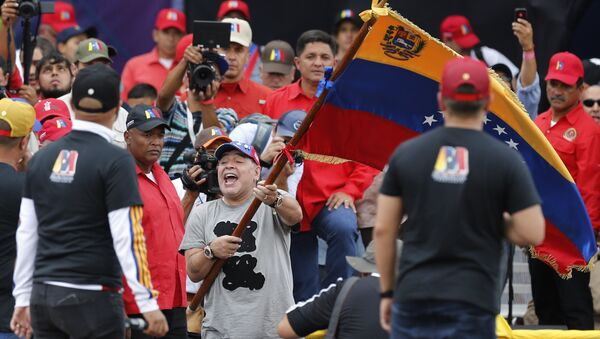 Argentina's former soccer star Diego Armando Maradona waves a Venezuelan flag during the closing campaign rally of President Nicolas Maduro in Caracas, Venezuela, Thursday, May 17, 2018. Maduro is seeking a new six-year mandate and despite crippling hyperinflation and widespread shortages of food and medicine, he is widely expected to win it in next May 20 election, that opponents have denounced as a fraud and have been condemned by much of the international community - Sputnik International
