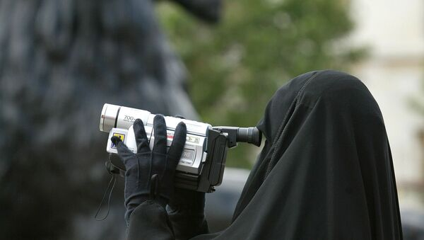A woman in traditional Muslim gowns videofilms her family under the watchful eyes of the lions guarding the Nelson column at Trafalgar square in London, 12 August 2002. - Sputnik International