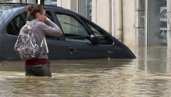 A woman walks on a flooded street caused by heavy rain and thunder storms, in Salies-de-Bearn, southwestern France, Wednesday, June 13, 2018 - Sputnik International
