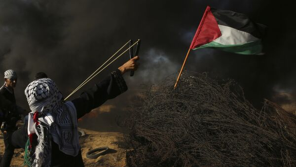 A female protester hurls a stone while others burn tires near the fence of the Gaza Strip border with Israel, during a protest east of Khan Younis, southern Gaza Strip, Friday, Aug. 10, 2018. Violence erupted at the Gaza border Friday after the territory's militant Islamic Hamas rulers and Israel appeared to be honoring a cease-fire that ended two days of intense violence amid efforts by neighboring Egypt to negotiate between the two sides - Sputnik International