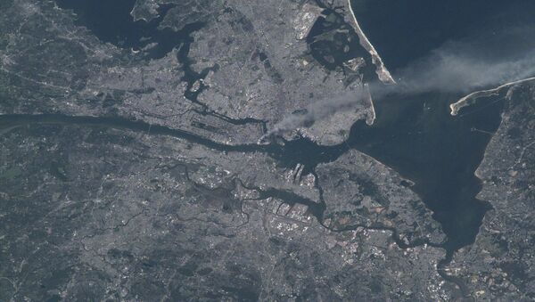 Visible from space, a smoke plume rises from the Manhattan area after two planes crashed into the towers of the World Trade Center. This photo was taken of metropolitan New York City (and other parts of New York as well as New Jersey) the morning of September 11, 2001. - Sputnik International