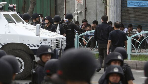 Uyghur protesters, sitting, are detained by security force officers after they marched to protest through the street in Urumqi, western China's Xinjiang province (File) - Sputnik International