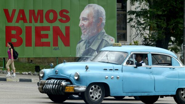 A taxi passes a sign with Cuban President Fidel Castro - Sputnik International