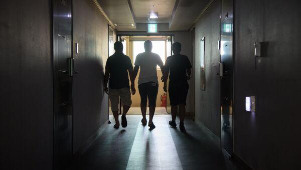A group of asylum seekers walk along a hallway (File) - Sputnik International