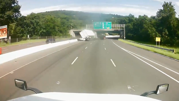 New Jersey police release footage showing the moment a tractor-trailer overturns following road rage incident - Sputnik International