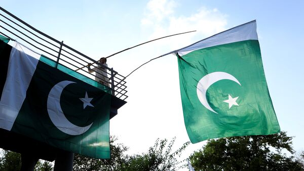 A boy uses a bamboo stick to adjust national flags at an overhead bridge ahead of Pakistan's Independence Day, in Islamabad, Pakistan August 10, 2018 - Sputnik International