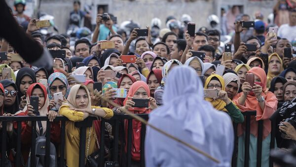 People use their mobile phones to take pictures as a Shariah law official whips a woman who is convicted of prostitution during a public caning outside a mosque in Banda Aceh, Indonesia, Friday, April 20, 2018. Indonesia's deeply conservative Aceh province on Friday caned several unmarried couples for showing affection in public and two women for prostitution before an enthusiastic audience of hundreds. The canings were possibly the last to be carried out before large crowds in Aceh after the province's governor announced earlier this month that the punishments would be moved indoors - Sputnik International
