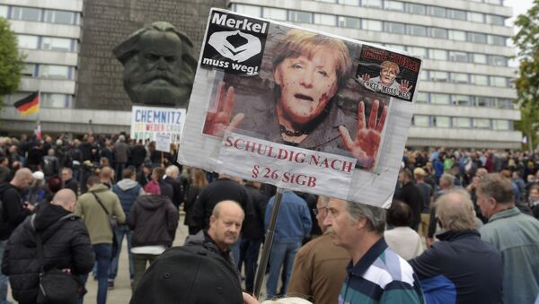A protestor holds a poster with a photo of Angela Merkel reading 'Merkel must go and referring she is guilty of incitement in Chemnitz, eastern Germany, Saturday, Sept. 1, 2018, after several nationalist groups called for marches protesting the killing of a German man last week, allegedly by migrants from Syria and Iraq - Sputnik International