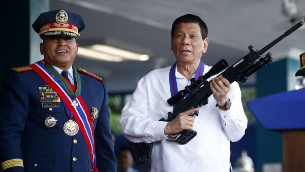 April 19, 2018 file photo, Philippine President Rodrigo Duterte, right, jokes to photographers as he holds an Israeli-made Galil rifle which was presented to him by former Philippine National Police Chief Director General Ronald Bato Dela Rosa at the turnover-of-command ceremony at the Camp Crame in Quezon city northeast of Manila - Sputnik International