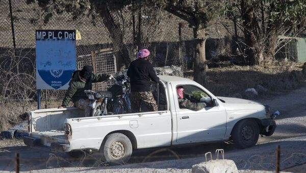 A group of men, not specified which group of rebels, drive into an abandoned UN post at Syria's Quneitra border crossing between Syria and the Israeli-controlled Golan Heights, seen from the Israeli-controlled Golan Heights, Monday, Nov. 28, 2016. - Sputnik International