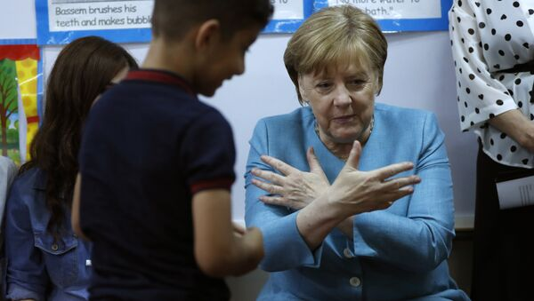 German Chancellor Angela Merkel, right, sits inside a classroom, as she speaks with Lebanese and Syrian displaced students where they studying together, during her visit to a Lebanese public school, in Beirut, Lebanon, Friday, June 22, 2018. Merkel is visiting Jordan and Lebanon, both neighbors of war-torn Syria, amid an escalating domestic row over migration - Sputnik International