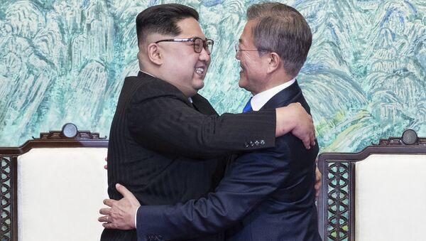 North Korean leader Kim Jong Un, left, and South Korean President Moon Jae-in embrace each other after signing on a joint statement at the border village of Panmunjom in the Demilitarized Zone, South Korea, Friday, April 27, 2018. - Sputnik International