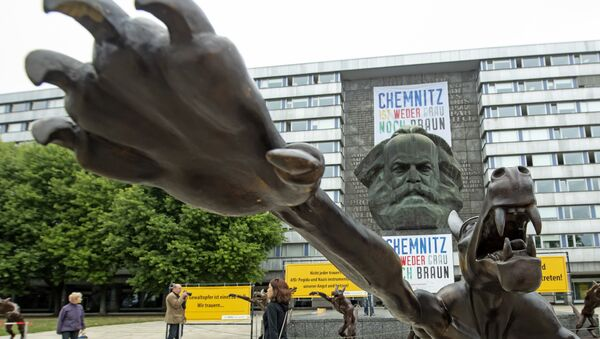 People walk between sculptures by artist Rainer Opolka in front of the Karl Marx Monument in Chemnitz, eastern Germany, Thursday, Sept. 13, 2018. The figure in the foreground is one of 10 life-sized metal wolf sculptures as a part of the spontan exhibition 'Wolves with Hitler salute howl in front of the Karl-Marx-Monument', to protest against xenophobia and right-wing extremism. - Sputnik International