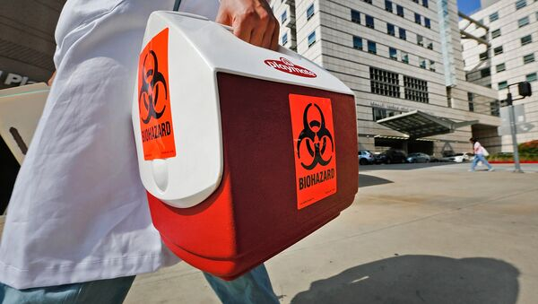 A research assistant with the David Geffen School of Medicine at UCLA carries a portable cooler marked with a biohazard label past the Ronald Reagan UCLA Medical Center in Los Angeles, Thursday, Feb. 19, 2015 - Sputnik International