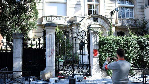 A French security officer takes a photograph outside the Iranian Embassy in the French capital Paris on September 14, 2018, after people taking part in a demonstration in a near by street split off and walked to the Iranian embassy where they sprayed red paint on the Embassy sign and trashed computers that were placed outside the embassy grounds for collection.  STEPHANE DE SAKUTIN / AFP - Sputnik International