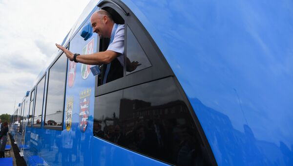 An employee of French train maker Alstom, waves from a window upon the arrival of Alstom's first hydrogen-powered train at the train station in Bremervoerde, Germany as it enters service on September 16, 2018.  Patrik STOLLARZ / AFP - Sputnik International