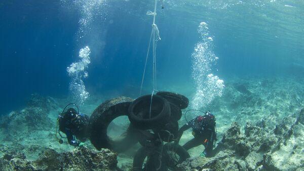 Дайверы поднимают автомобильные покрышки, найденные на дне Саронического залива вблизи Афин - Sputnik International