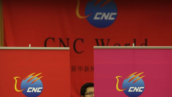 A Chinese employee of China Xinhua News Network Corp. (CNC) looks on during a media conference on the launching of its global, English-language television channel in Beijing Thursday, July 1, 2010. - Sputnik International