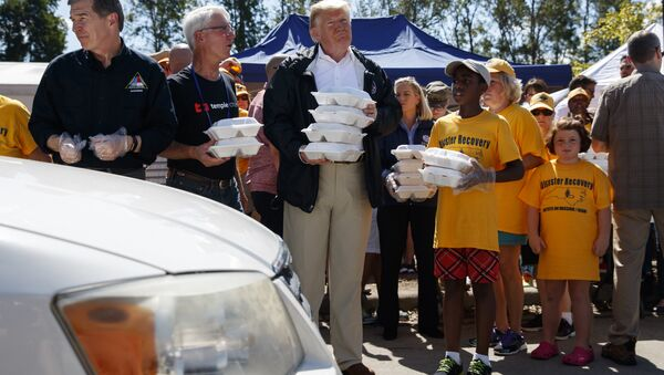 President Donald Trump hands out prepackaged meals to people in cars at Temple Baptist Church in an area impacted by Hurricane Florence. - Sputnik International