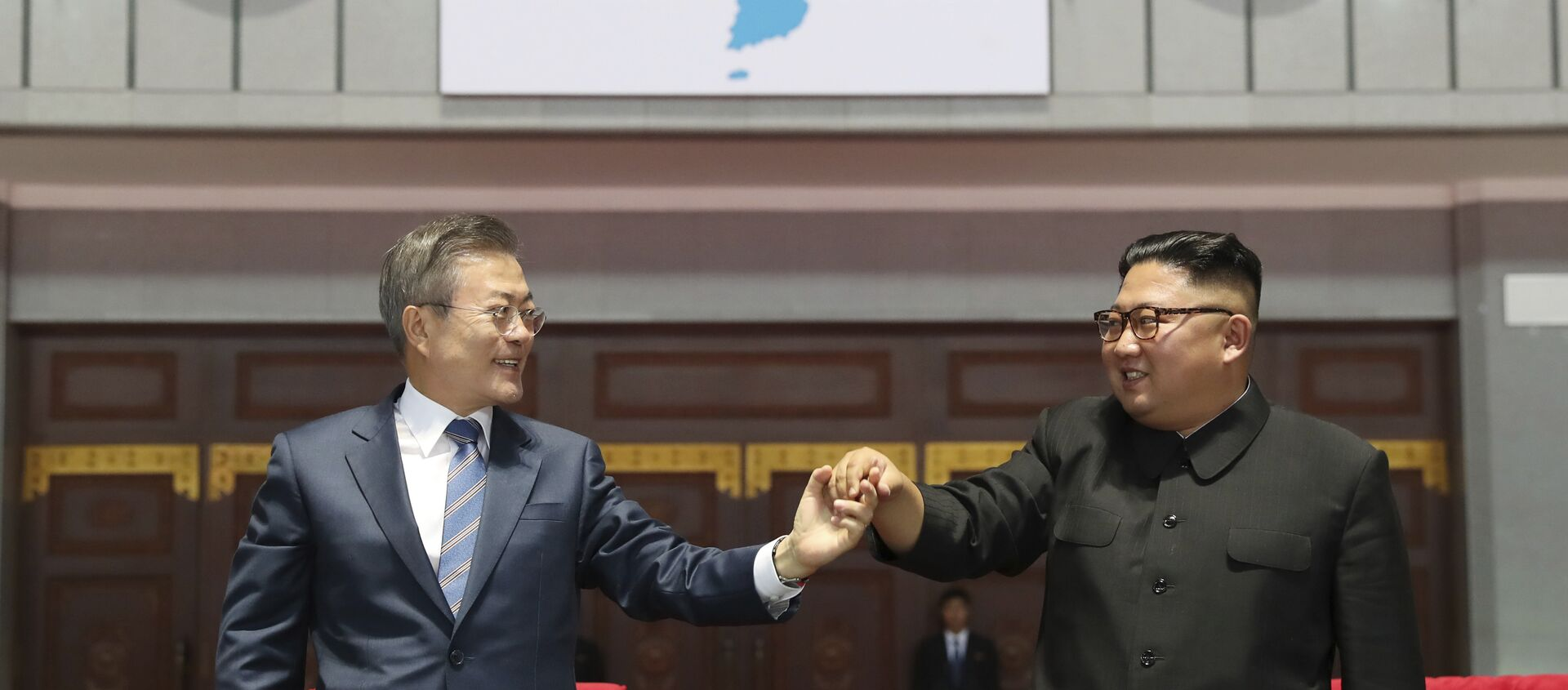 South Korean President Moon Jae-in, left, and North Korean leader Kim Jong Un hold their hands after watching the mass games performance of The Glorious Country at May Day Stadium in Pyongyang, North Korea, Wednesday, Sept. 19, 2018. Unification flag symbol at top centre. - Sputnik International, 1920, 30.07.2021