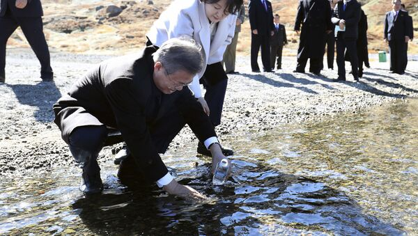 South Korean President Moon Jae-in puts water from the crater lake into a bottle as his wife Kim Jung-sook watches on Mount Paektu - Sputnik International