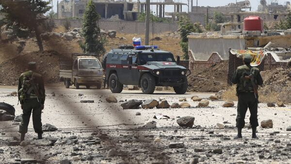 Syrian army soldiers stand guard as Russian military police vehicle passes by near the town of Alhureyeh, Syria, Tuesday, Aug. 14, 2018 - Sputnik International