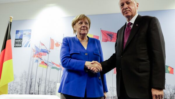 German Chancellor Angela Merkel, left, and Turkish President Recep Tayyip Erdogan, right, shake hands prior to a bilateral meeting on the sideline of a summit of heads of state and government at NATO headquarters in Brussels Wednesday, July 11, 2018 - Sputnik International