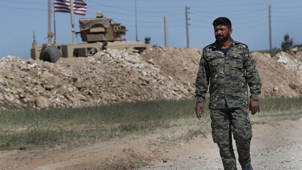 In this April 4, 2018 file photo, a U.S-backed Syrian Manbij Military Council soldier passes a U.S. position near the tense front line with Turkish-backed fighters, in Manbij, north Syria - Sputnik International
