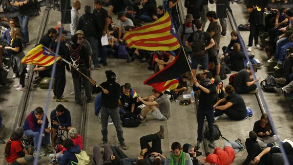 Activists advocating for Catalan secession wave Catalonian independence flags as others sit on the railway tracks at the station in Girona, Spain, Monday Oct. 1, 2018 - Sputnik International
