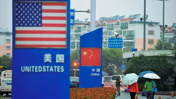 Signs with the US flag and Chinese flag are seen outside a store selling foreign goods in Qingdao in China's eastern Shandong province on September 19, 2018 - Sputnik International