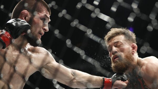 Khabib Nurmagomedov, left, punches Conor McGregor during a lightweight title mixed martial arts bout at UFC 229 in Las Vegas, Saturday, Oct. 6, 2018. - Sputnik International