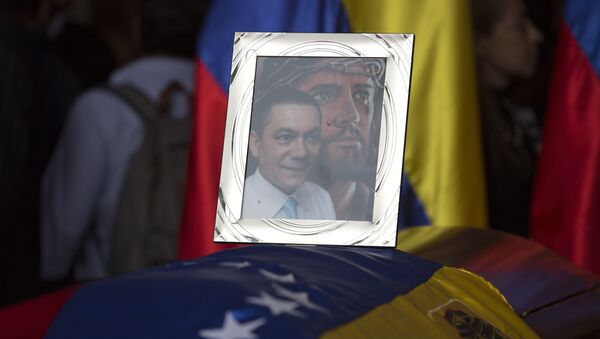 A framed portrait of opposition activist Fernando Alban shadowed by an image of Jesus Christ sits on the flag-draped casket containing his remains, during a solemn ceremony at the National Assembly headquarters, in Caracas, Venezuela, Tuesday, Oct. 9, 2018 - Sputnik International
