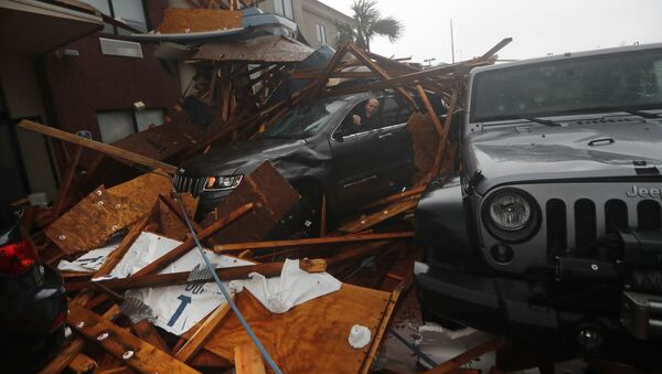 A storm chaser climbs into his vehicle during the eye of Hurricane Michael to retrieve equipment after a hotel canopy collapsed in Panama City Beach, Fla., Wednesday, Oct. 10, 2018 - Sputnik International