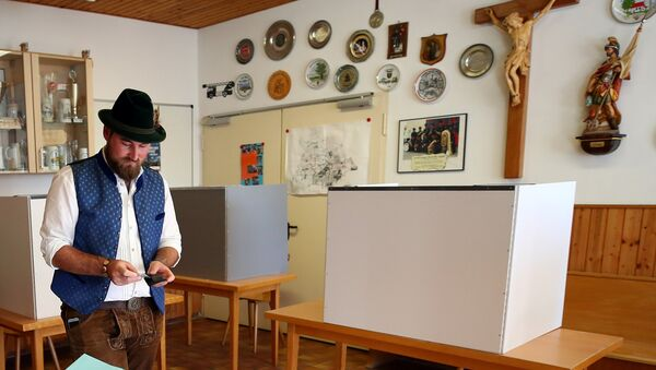 A man in traditional clothes casts his vote for the Bavarian state elections at a polling station in Maisach, Germany - Sputnik International