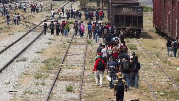 Immigrants walk along the rail tracks after getting off a train during their journey toward the US-Mexico border in Ixtepec, southern Mexico - Sputnik International